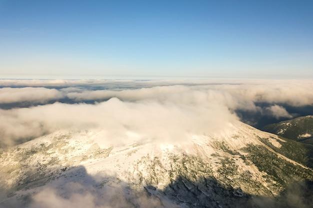 Widok z góry na białe podpuchnięte chmury pokrywające ośnieżone szczyty gór w jasny, słoneczny dzień.