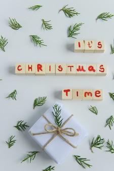 Widok z góry na białe pudełko na prezenty rękodzieła z drewnianymi literami w czasie świąt bożego narodzenia i świeżą gałązką jodły