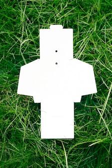 Widok z góry na białe puste rozłożone pudełko na akcesoria lub metki odzieżowe na zielonej trawie latem z ...
