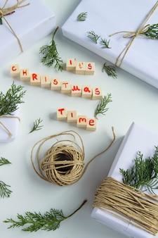 Widok z góry na białe rzemieślnicze pudełka na prezenty z drewnianymi literami w czasie świąt bożego narodzenia i świeżymi otrębami jodłowymi