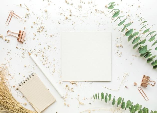 Widok z góry na biały papier na stole roboczym z makietami akcesoriów i suchym kwiatem.