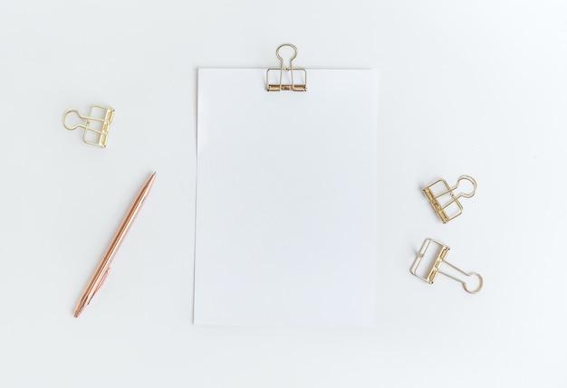 Widok z góry na biały papier notatkowy ze spinaczem na stole roboczym. minimalistyczny styl dla kreatywności