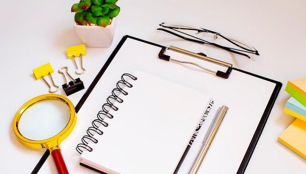 Widok z góry na biały pulpit z ładnie zorganizowanymi narzędziami biurowymi i elektronicznymi gadżetami i lupą