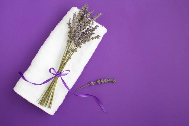 Widok z góry na biały ręcznik i bukiet lawendy suchej na fioletowym tle