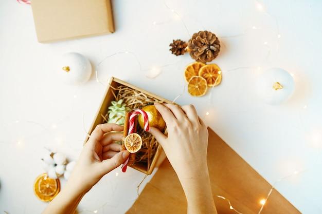 Widok z góry na biały stół ze świątecznymi dekoracjami papier pakowy szyszki jodłowe suszone pomarańcze ręka kobiety ...