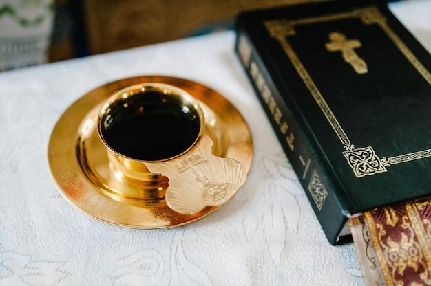 Widok z góry na biblię i wino, krew bożą w kielichu przed ceremonią ślubną w kościele.