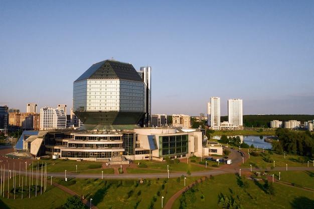 Widok z góry na bibliotekę narodową i nową dzielnicę z parkiem w mińsku - stolicy republiki białorusi o zachodzie słońca, budynek publiczny.