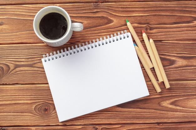 Widok z góry na biurko biurka. notatnik z pustych stron na drewnianym stole
