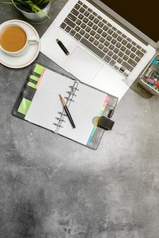 Widok z góry na biurko biznesowe z laptopem, kawą, rośliną doniczkową, notatnikiem i akcesoriami biznesowymi