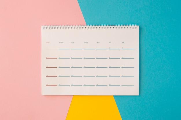 Widok z góry na biurko kalendarza na kolorowym tle