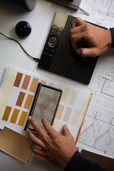 Widok z góry na biurko projektanta wnętrz ręce mężczyzny pracują z tabletem graficznym i rysunkami
