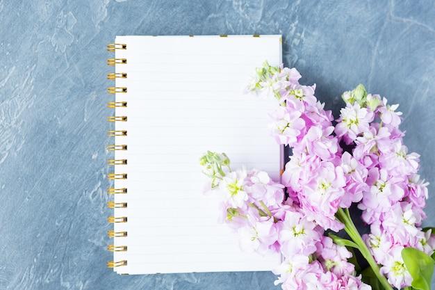 Widok z góry na biurko, pusty notatnik z widokiem na fioletowe kwiaty, płaski układ. skopiuj miejsce