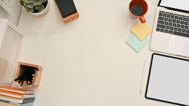 Widok z góry na biurko w domu z tabletem, laptopem, papeterią i miejscem na kopię na stole, ścieżkę przycinającą