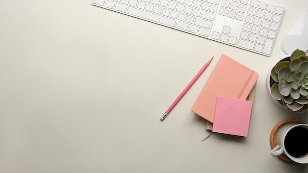 Widok z góry na biurko z klawiaturą komputerową, papeterią, filiżanką kawy, doniczką i miejscem na kopię