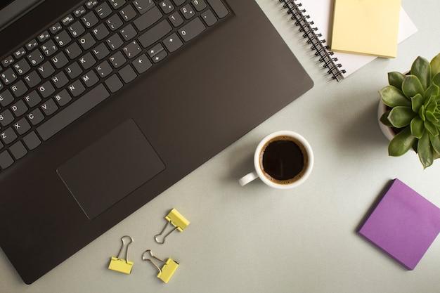 Widok z góry na biurko z laptopem, filiżanką kawy, kaktusem i papeterią na szarym stole. płaskie ukształtowanie biurka w miejscu pracy.