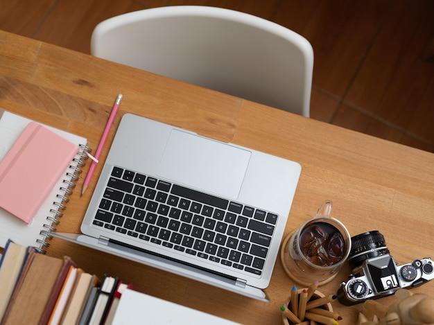 Widok z góry na biurko z laptopem, papeterią, aparatem, książkami, filiżanką kawy i białym krzesłem w pokoju biurowym