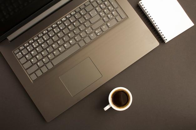 Widok z góry na biurko z laptopem, pusty notatnik i filiżankę kawy na czarnym stole. płaskie ukształtowanie biurka w miejscu pracy.