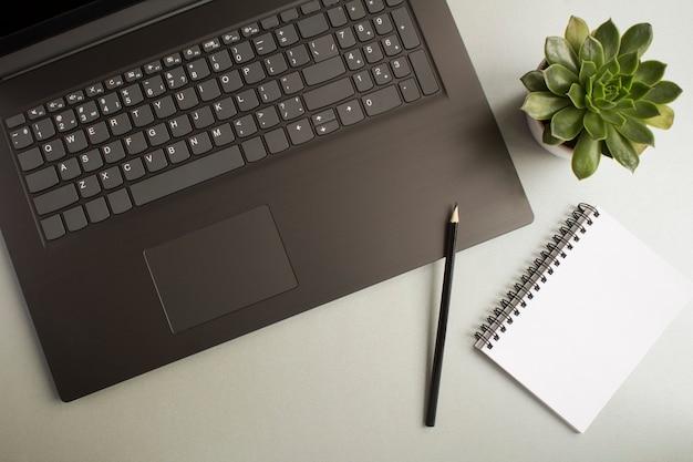 Widok z góry na biurko z laptopem, pusty pusty notatnik i kaktus na szarym stole. płaskie ukształtowanie biurka w miejscu pracy.