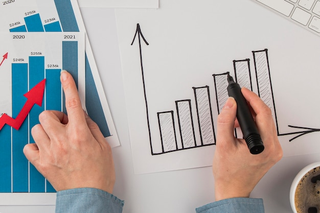 Widok z góry na biurko z wykresem wzrostu i rękami
