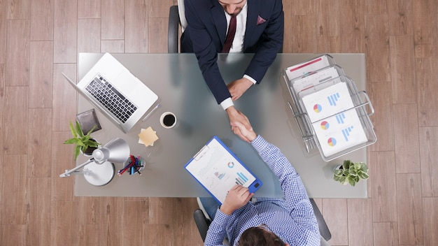 Widok z góry na biznesmenów ściskających dłonie podczas negocjacji biznesowych w biurze startowym