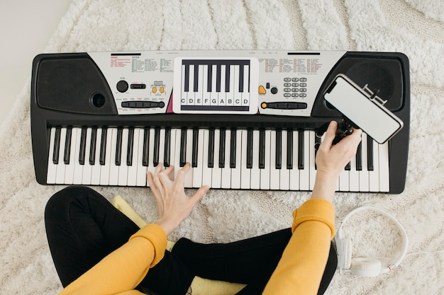 Widok z góry na blogerkę-muzyk przesyłający strumieniowo w domu ze smartfonem
