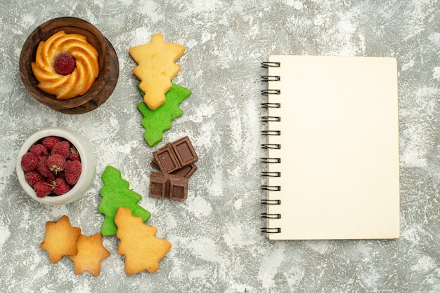 Widok z góry na boże narodzenie drzewo ciasteczka miska z malinami czekoladki notebook na szarym stole