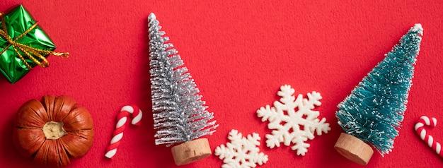 Widok z góry na boże narodzenie projekt koncepcja wakacje ozdoba ozdoba skład z choinką, gwiazda prezent z miejsca kopiowania na białym tle na czerwonym stole.
