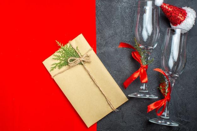 Widok z góry na boże narodzenie tło z kieliszkami szklanymi czapki świętego mikołaja i prezent na czerwonym i czarnym tle