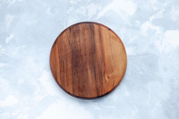 Widok z góry na brązowe drewniane biurko, okrągłe na jasnym biurku, drewniane drewniane