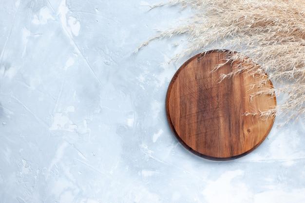 Widok z góry na brązowe okrągłe biurko do jedzenia na lekkich, drewnianych drewnianych produktach