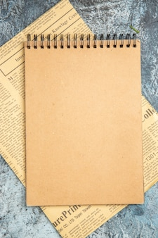 Widok z góry na brązowy notatnik na gazecie na szarym tle