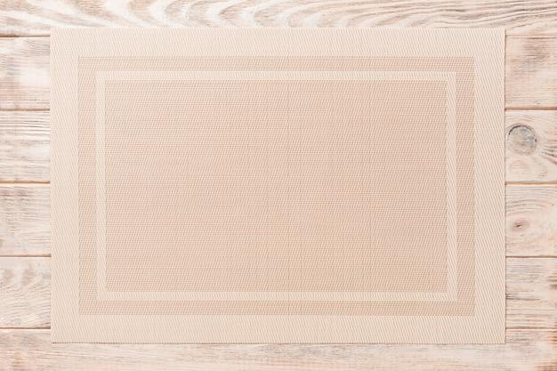 Widok z góry na brązowy obrus do jedzenia na drewnianym.