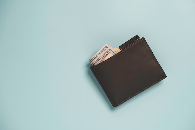 Widok z góry na brązowy skórzany portfel pieniądze z banknotu samodzielnie na niebiesko.