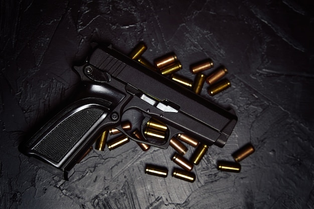 Widok z góry na broń palną pistolet i pociski na ciemnym tle pistolet do obrony lub ataku koncepcja krym...