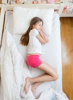 Widok z góry na brunetki w różowej piżamie śpiące na łóżku