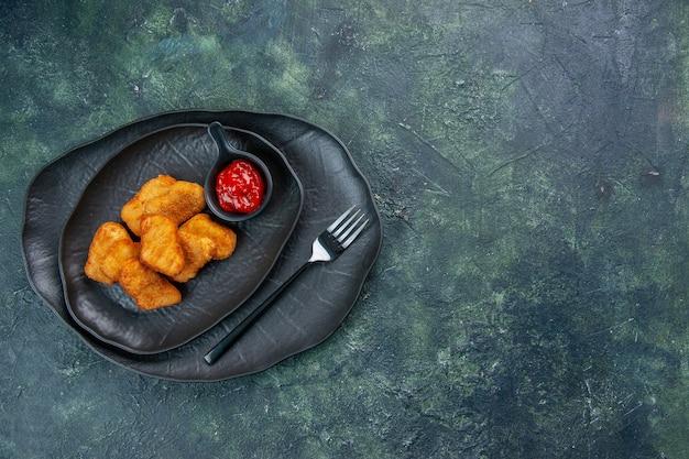 Widok z góry na bryłki kurczaka i widelec keczupowy w czarnych talerzach po prawej stronie na ciemnej powierzchni