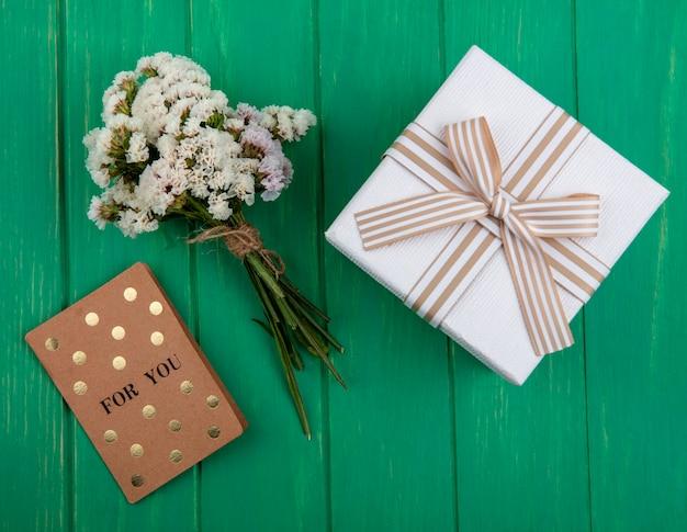 Widok z góry na bukiet białych kwiatów z brązową kartą i prezent w białym opakowaniu z kokardką na zielonej powierzchni