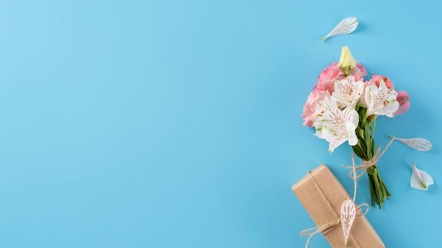 Widok z góry na bukiet kwiatów z pudełkiem prezentowym i miejscem na kopię copy