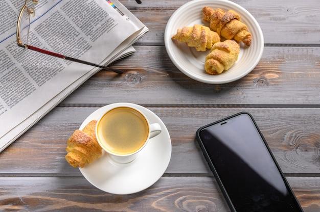 Widok z góry na bułeczki z kawą i ciasteczkami domowej roboty na drewnianej powierzchni w pobliżu gazety smartfona i okularów