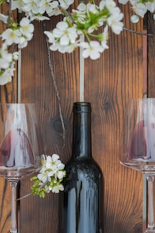 Widok z góry na butelkę czerwonego wina i wiśniowych okularów na drewnianym stole. klasyczne wino i kwiaty wiśni.