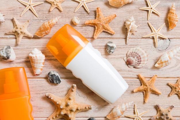 Widok z góry na butelkę z filtrem przeciwsłonecznym z muszelek i rozgwiazdy na tle drewnianej deski z miejsca kopiowania. mieszkanie świeckich koncepcji letnich podróży wakacyjnych