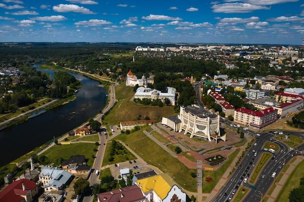 Widok z góry na centrum miasta grodno na białorusi. historyczne centrum z dachem pokrytym czerwoną dachówką, zamkiem i operą.