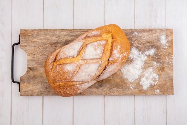 Widok z góry na chrupiący chleb z mąki na deskę do krojenia na podłoże drewniane