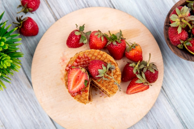 Widok z góry na ciastka waflowe i truskawki w talerzu i misce oraz na powierzchni drewnianych