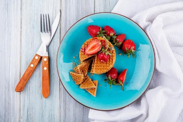 Widok z góry na ciastka waflowe i truskawki w talerzu z widelcem i nożem na szmatce i powierzchni drewnianej