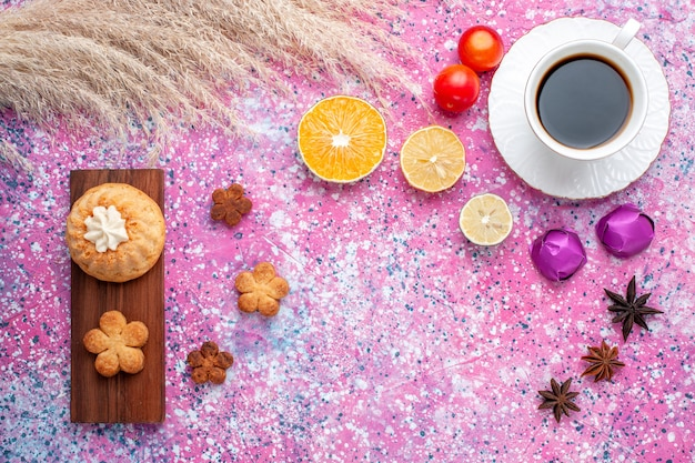 Widok z góry na ciastko z filiżanką herbaty i plasterkami pomarańczy na różowej powierzchni