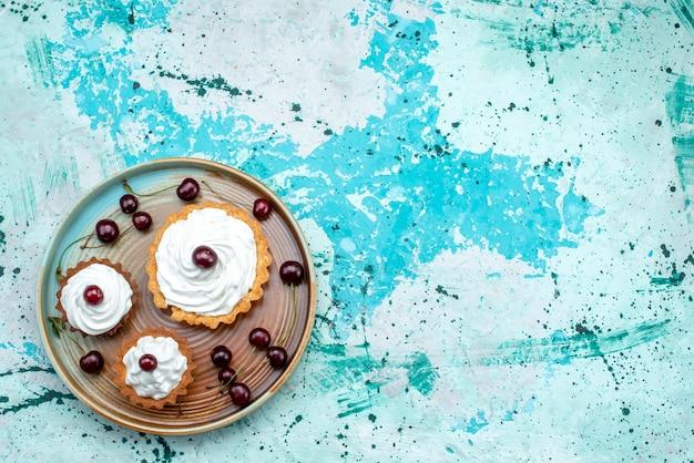 Widok z góry na ciastko z kremową powierzchnią i wiśniami