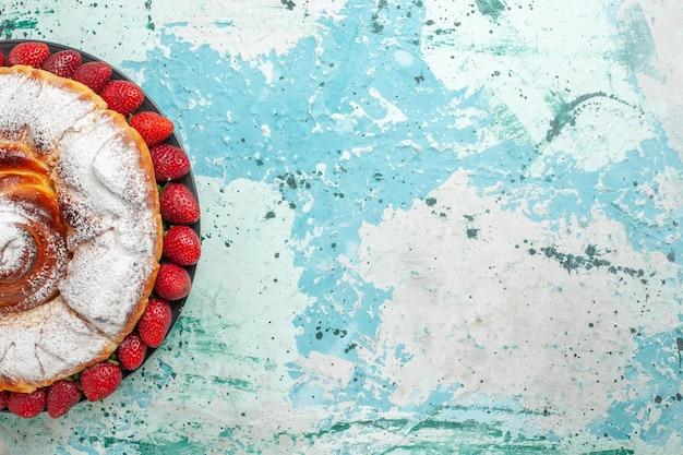 Widok z góry na ciasto cukrowe w proszku ze świeżymi czerwonymi truskawkami na jasnoniebieskim biurku