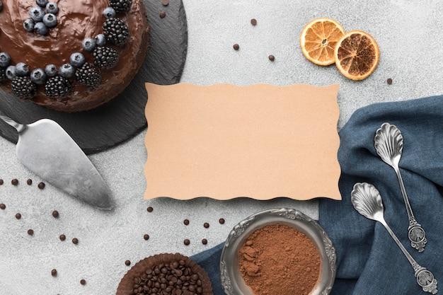 Widok z góry na ciasto czekoladowe z jagodami i łyżkami