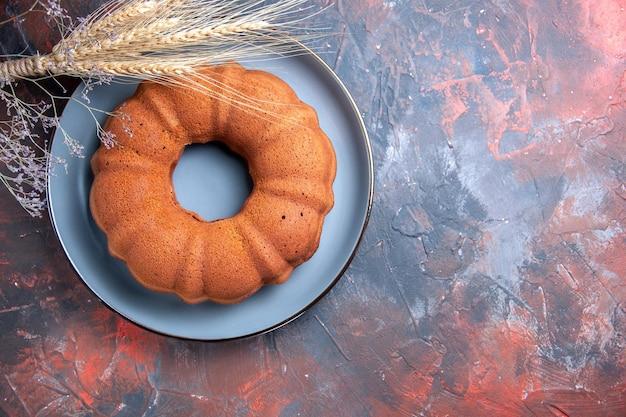 Widok z góry na ciasto niebieski talerz z kłosami pszennymi i gałęziami drzew